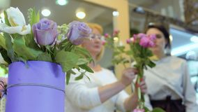 Two women create flower bouquet in flower shop. Florist teach assistant to make flower bouquet. Woman wearing black protective gloves help assistant to create a stock video
