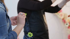 Two women create garlands from flowers and metal wire in art studio. They accurately fasten little blossoms with each other trying to follow instructions that stock video footage