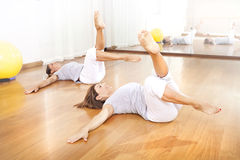 Two women crossing legs in synchrony for fitness royalty free stock images