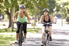 Two Women Cycling Through Park Royalty Free Stock Image