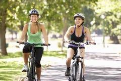 Two Women Cycling Through Park Stock Photos