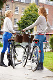 Two Women Cycling Through Urban Park Together Royalty Free Stock Images