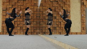 Two women dance belly dance in front of mirror inside studio. Hot brunette in black costume with long wavy hair dances, turns head, moves hips. Sexy dark stock video footage