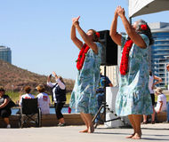 Two Women Dance During The Dragon Boat Festival. Two women dance to Hawiian music, wearing print dresses and lei, during the Dragon Boat Festival at Tempe Town royalty free stock photography