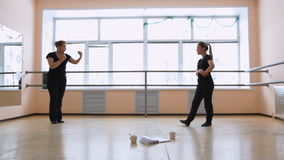 Two women, dancers in black clothes come up with a new dance. Dancing in the hall. General plan stock video