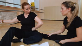 Two women, dancers in black clothes come up with a new dance. on the floor. Two women, dancers in black clothes come up with a new dance. Write in a notebook stock video footage