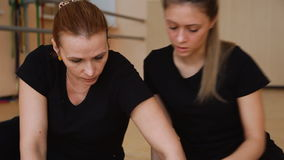 Two women, dancers in black clothes come up with a new dance. on the floor. Two women, dancers in black clothes come up with a new dance. Write in a notebook stock video