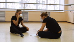 Two women, dancers in black clothes come up with a new dance. on the floor. Two women, dancers in black clothes come up with a new dance. Write in a notebook stock footage