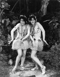 Two women dancing in grass skirts Stock Image