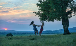 Two women dancing on the grass at sunset Stock Photos