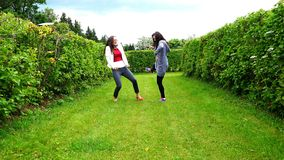 Two women dancing happily on the grass waving their arms and legs.  stock footage