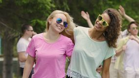 Two women dancing, hugging, enjoying concert with friends in park, youthfulness