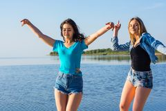 Two women are dancing on the seashore, holding hands and laughing. Friends are dancing on a seashore, holding hands and laughing. Young people, two women stock photos
