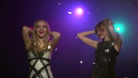 Two women dancing, send blowing kisses. Close-up. Slow motion. Two young women in tight short dresses dancing in a disco style, make hand movements and send stock video