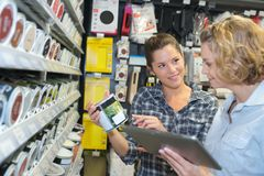 Two women in deco home painting department at hardware store. Buying Royalty Free Stock Photos
