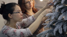 Two women decorate artificial fir tree covered with frost. Adult Asian woman with dark hair in white sweater with pink roses with green leaves put transparent stock video footage