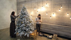 Two women decorate artificial fir tree covered with frost. Christmas tree decorated with a lot of gold, silver, snow balls, pine cones stand in loft room stock video