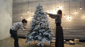 Two women decorating Christmas tree with smiling and talking. They go around the Christmas tree hanging decorations and toys that would prepare for the New stock video