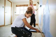 Two Women Decorating Room In New Home Painting Wall stock image