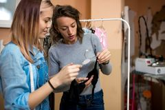 Two women, designer clothes and customer, in the workshop. Two women, the designer of clothes and the customer discuss a model of a bra stock photo