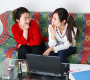 The two women are dialogue. Two women chat in front of the computer Stock Photo