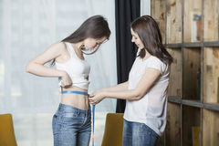 Two women are on a diet is to measure the levels of the waist to Royalty Free Stock Photography