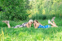 Two women of different generations lie on the grass. Mother and daughter. Grandmother and granddaughter   Grandmother and granddau Stock Photography