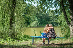 Two women of different generations sitting on a bench near a pond in the summer. Mother and daughter hugging. Grandmother and gran Stock Photos