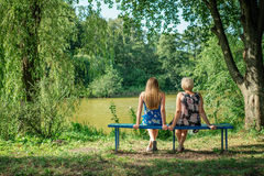 Two women of different generations sitting on a bench near a pond in the summer. Mother and daughter hugging. Grandmother and gran Stock Photo