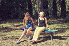 Two women of different generations sitting on a bench and talking Stock Photos