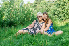 Two women of different generations sitting on the grass in the summer. Mother and daughter hugging. Grandmother and granddaughter. Royalty Free Stock Photos