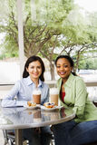 Two Women Dining Out. Two smiling woman sitting enjoying muffins and coffee drinks at a cafe. Vertical shot royalty free stock photo