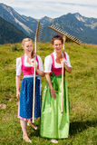Two women in dirndl with rakes have fun at work. Two bavarian women in dirndl with rakes on their shoulders having fun in a meadow in the mountains Stock Image