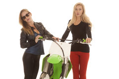 Two women by a dirt bike one in glasses Royalty Free Stock Photo