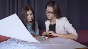 Two women discuss blueprint while sitting in modern office. Two women discuss blueprint while sitting in modern office stock video footage