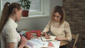 Two women discuss chart . Two women sitting near the window in the office and  discuss chart  and diagram stock footage
