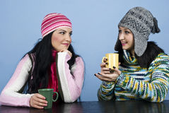 Two women discuss and enjoy a hot drink Stock Images