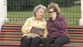 Two women discuss about home problems outdoors. Two women sit and discuss about home problems outdoors. One woman aged 80s dressed in yellow jacket holds stock footage