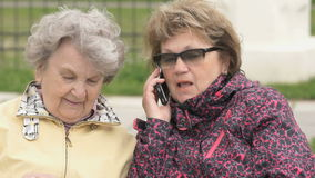 Two women discuss about home problems outdoors. Two women sit and discuss about home problems outdoors. One woman dressed in sport jacket talking with relatives stock footage