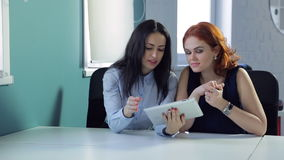 Two women discuss outfits on tablet during a break between work. Colleagues looking at electronic device sitting talking about clothes. Beautiful ladies in stock video