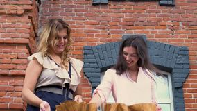 Two women discuss samples of fabrics at office on a terassa. The girl talks to the customer in the open air. On this video you can see as the woman shows to the stock video