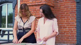Two women discuss samples of fabrics at office on a terassa. The girl talks to the customer in the open air. The woman. On this video you can see as the woman stock footage