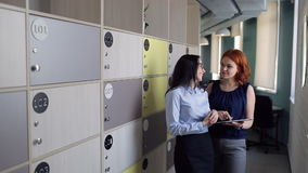 Two women discuss something in office near storage cells. Woman with short red hairstyle, many silver rings, necklace, earnings diamonds denim top, grey stock video