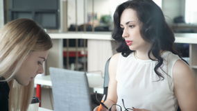 Two women discuss something sitting at table in office. Attractive woman with brown eyes, red full lips, dark curly long hair in white transparent blouse with stock video footage