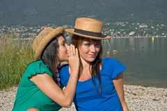 Two women discussing. Woman speaking in the ear of another woman Royalty Free Stock Photo