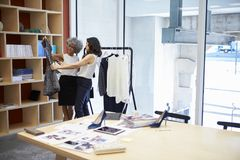 Free Two Women Discussing Clothes In A Creative Media Office Stock Images - 108952464
