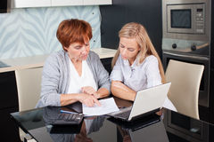 Two women discussing documents at home. Consultant with woman Stock Image