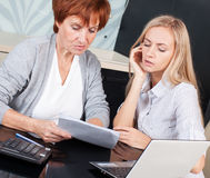 Two women discussing documents at kitchen Stock Image