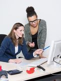 Two women are discussing in front of the computer at office. Two business women are discussing in front of the computer in the office. Both women are looking to Stock Photos