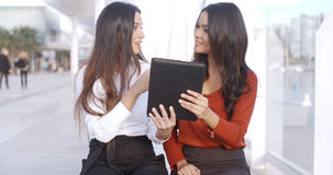 Two women discussing information on a tablet. Two women sitting outdoors on a high key urban esplanade discussing information on a tablet computer which they are Royalty Free Stock Image